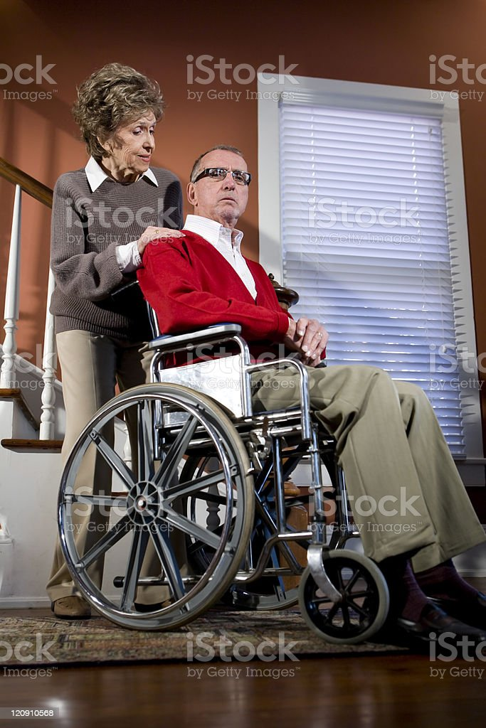 Senior couple at home, man in wheelchair royalty-free stock photo