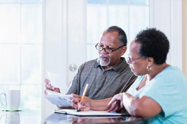 Senior couple at home paying bills stock photo