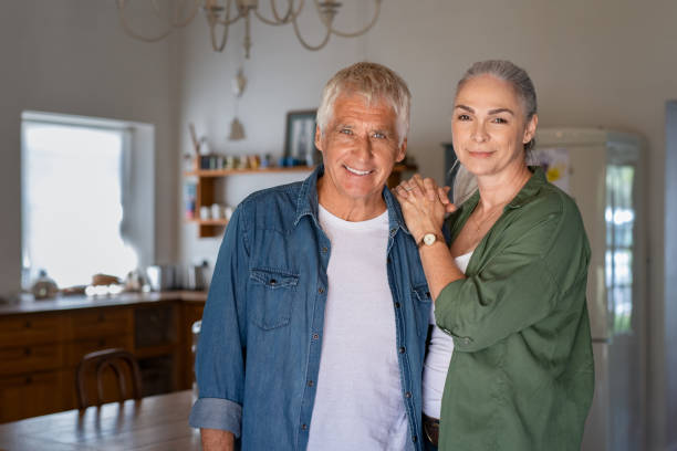 Senior couple at home Senior man and woman standing in new house looking at camera. Portrait of old couple relaxing at home. Elderly husband and mature wife looking at camera. mature couple stock pictures, royalty-free photos & images