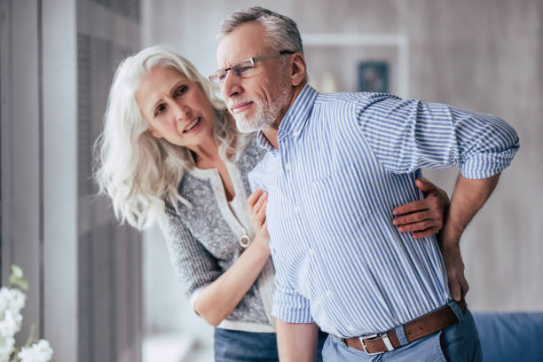 Senior couple at home Senior couple at home. Handsome old man is having back pain and his attractive old woman supports him. back pain stock pictures, royalty-free photos & images