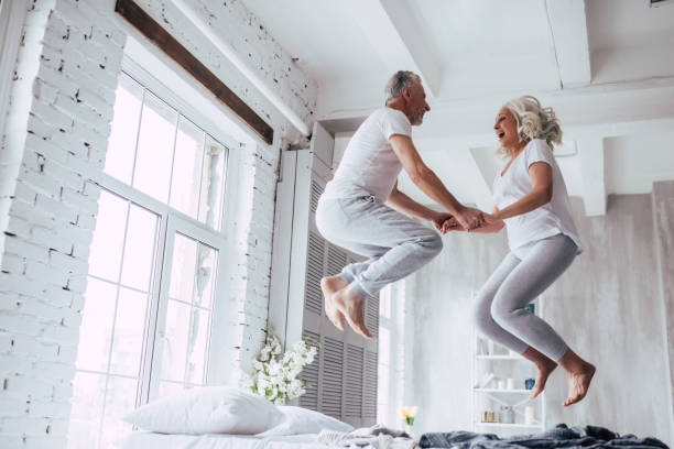 Senior couple at home Love lives forever! Senior couple at home. Handsome old man and attractive old woman are enjoying spending time together. Having fun and jumping in bed. couple in bed stock pictures, royalty-free photos & images