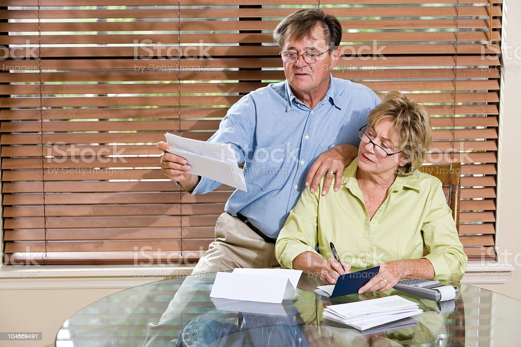 Senior couple at home reviewing finances, paying bills together stock photo
