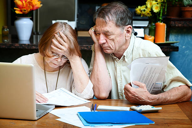 senior couple at home with many bills - elder money stock pictures, royalty-free photos & images