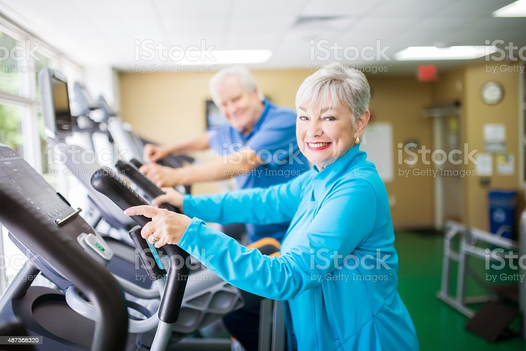 Senior couple at the elliptical machines stock photo