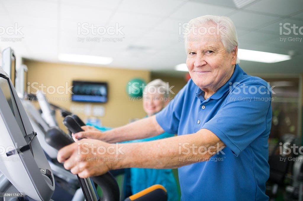 Senior couple at the elliptical machines stock photo