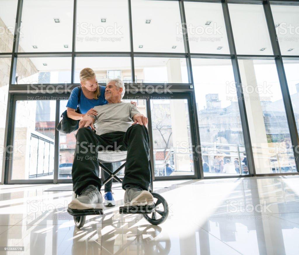 Couple de personnes âgées à l'hôpital et l'homme assis sur un fauteuil roulant, tandis que le partenaire embrasse - Photo