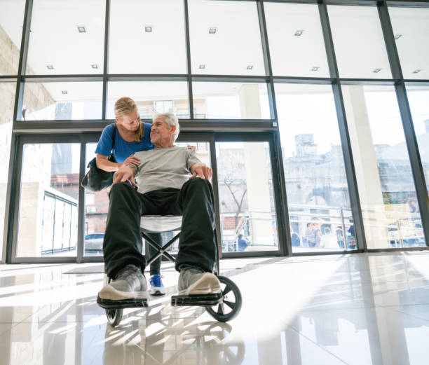 Senior couple at the hospital and man sitting on a wheelchair while partner hugs him - foto stock