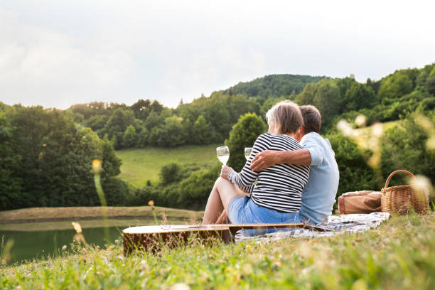 senior couple at the lake having a picnic - couple lap stock photos and pictures