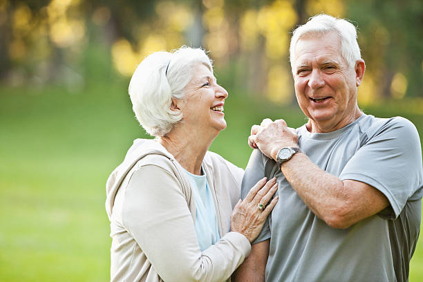 senior couple at the park - 60 69 years stock photos and pictures