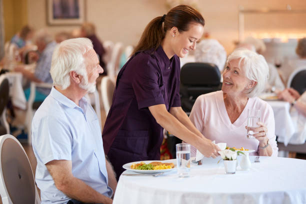 Senior Couple Being Served With Meal By Carer In Dining Room Of Retirement Home Senior Couple Being Served With Meal By Carer In Dining Room Of Retirement Home retirement community stock pictures, royalty-free photos & images