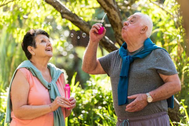 Senior couple blowing bubbles outdoors stock photo
