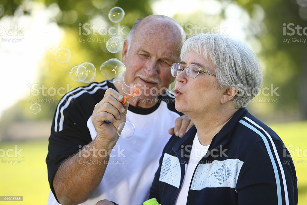Senior couple blowing bubbles royalty-free stock photo