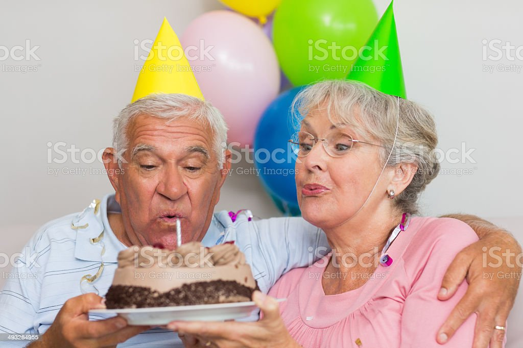 Senior Couple Blowing Out Candles On Birthday Cake Royalty Free Stock Photo