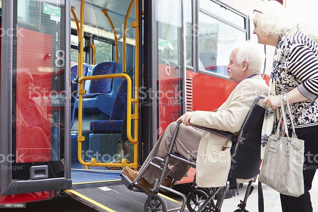 Senior Couple Boarding Bus Using Wheelchair Access Ramp stock photo