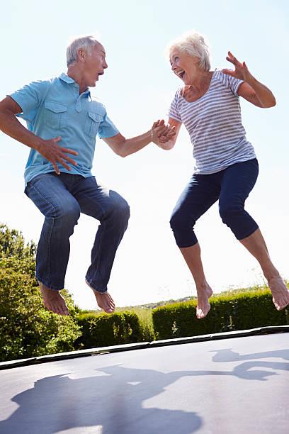 altes paar auf und ab springen auf trampolin im garten - gartentrampolin stock-fotos und bilder