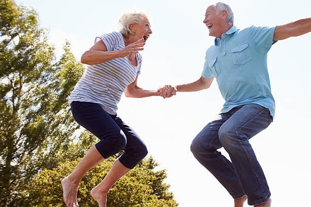 Senior Couple Bouncing On Trampoline In Garden Senior Couple Bouncing On Trampoline In Garden Laughing young at heart stock pictures, royalty-free photos & images