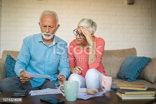 istock Senior couple brainstorming the solution to a financial problem 1074329036