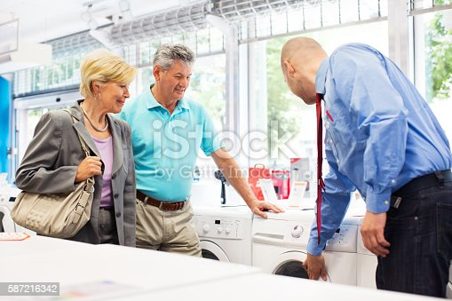 Shop assistant showing washing machine to senior couple at appliance store