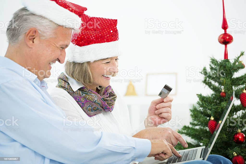 senior couple buying christmas gifts on internet royalty free stock photo