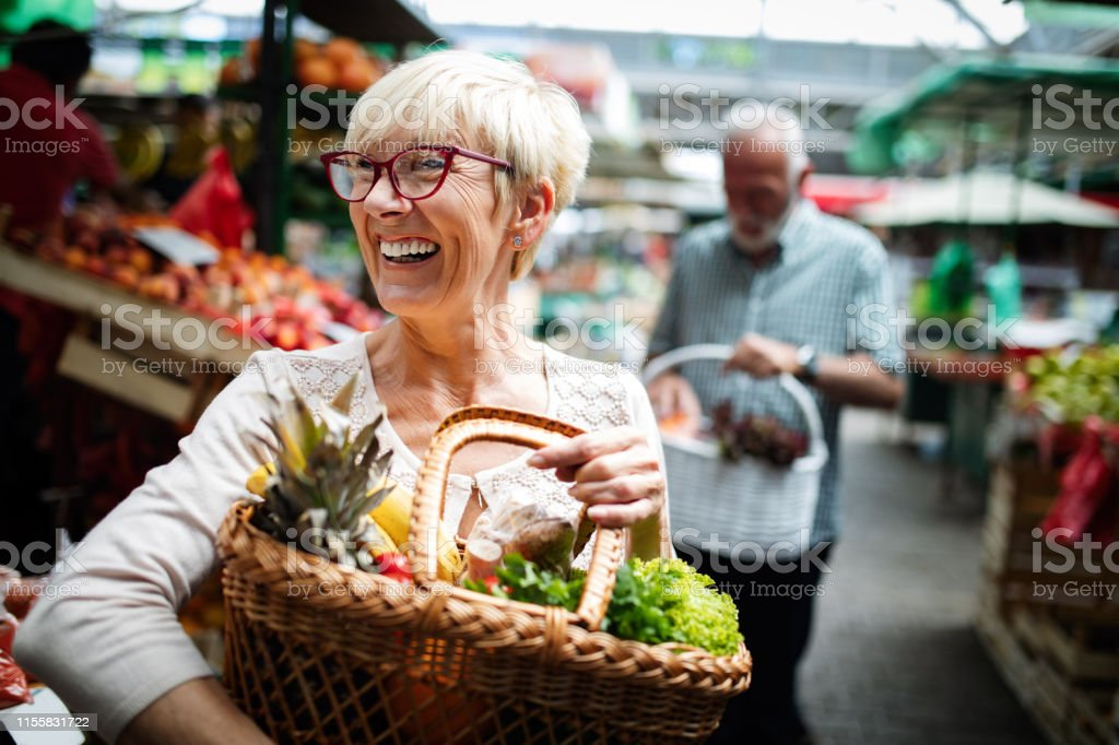 Senior couple buying fresh vegetables and fruits at the local market - Foto stock royalty-free di Adulto