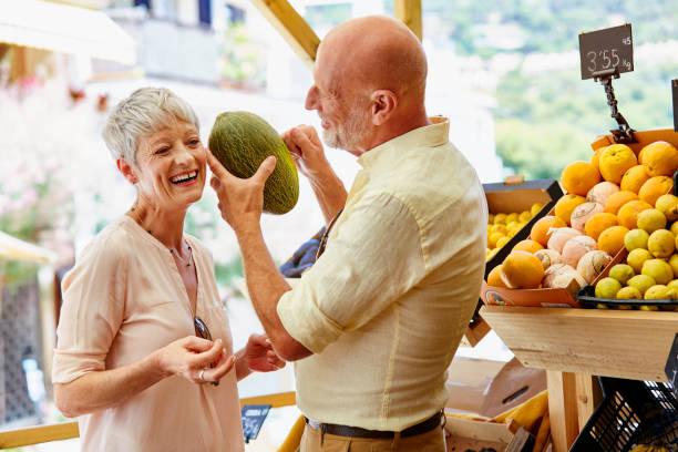 älteres paar gemüse im store kaufen - kürbis kaufen stock-fotos und bilder
