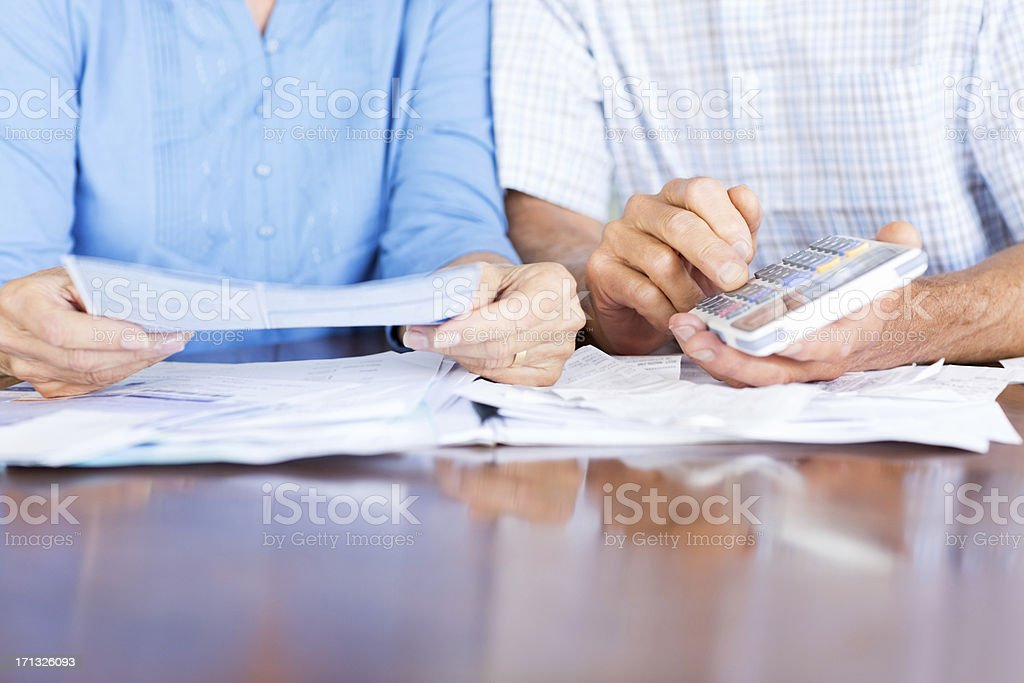 Midsection of senior man and woman calculating expenses at home....