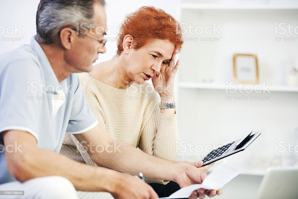 Senior couple calculating their monthly finances at home. stock photo