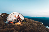 istock Senior couple camping in the mountains and eating a snack 1031972950
