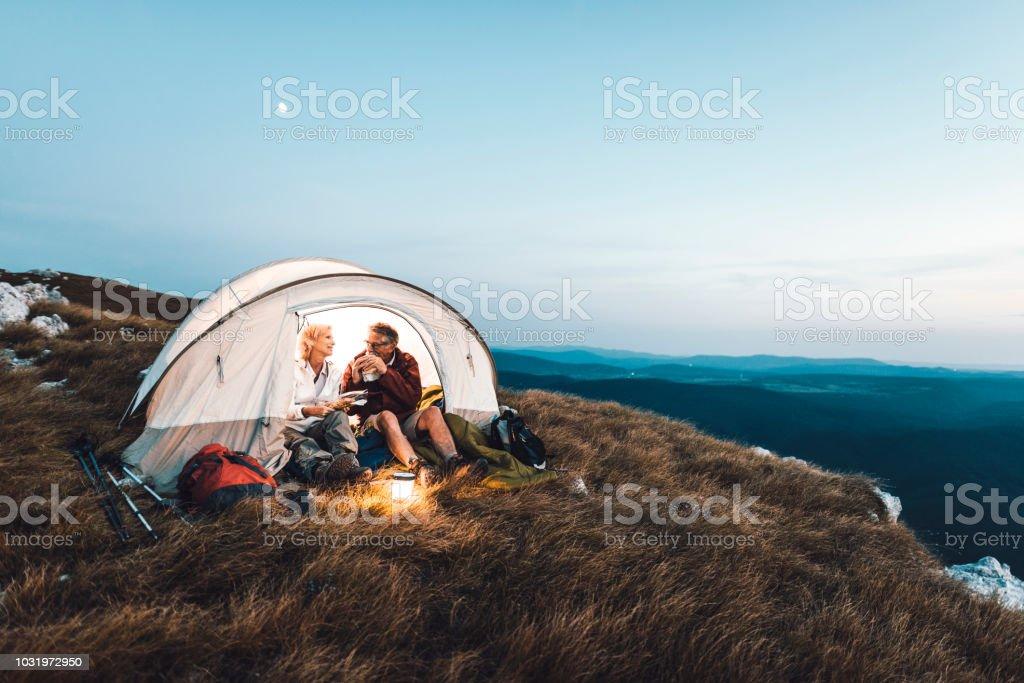 Älteres Paar camping in den Bergen und einen Snack zu essen – Foto