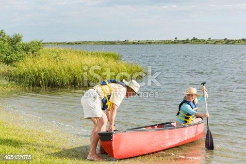 istock Senior couple canoeing, at edge of lake 465422075