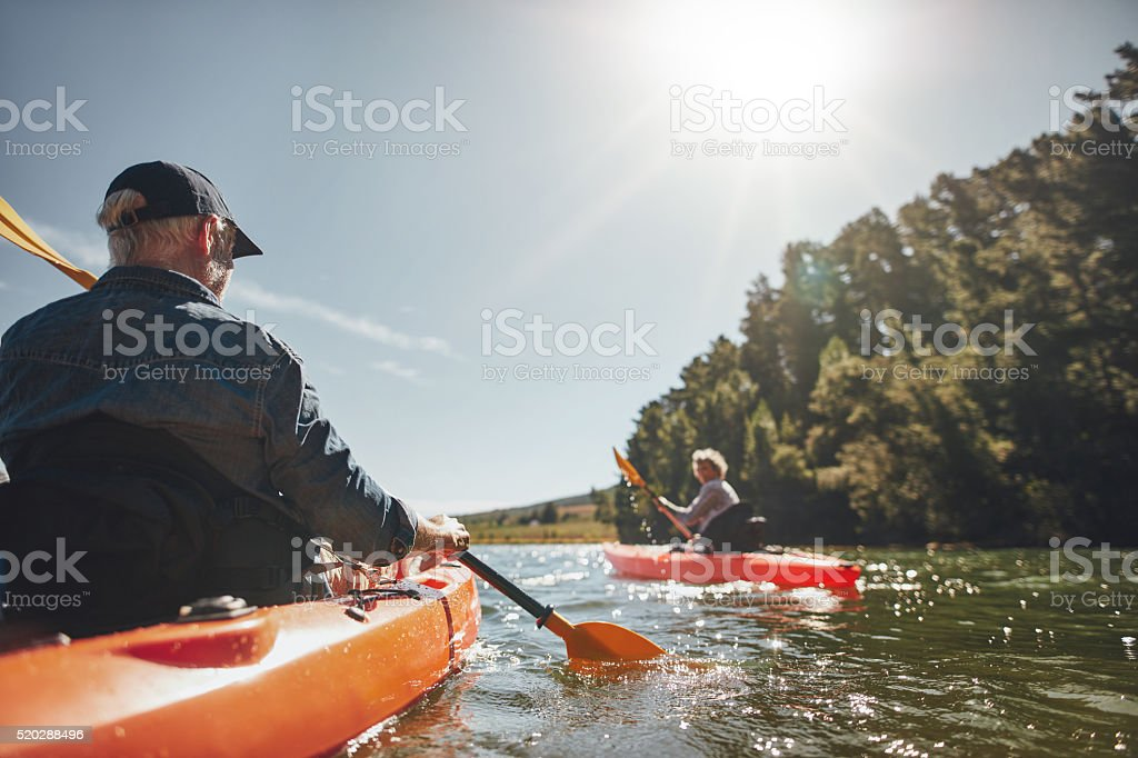 Senior couple canoeing in the lake stock photo