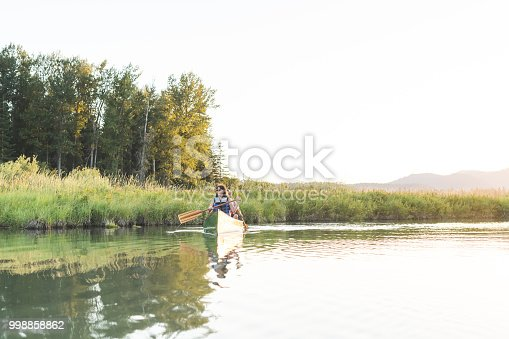 A Caucasian couple spend a summer afternoon canoeing around a beautiful lake. There are mountains and forest in the background and the sun is setting on a lovely day.