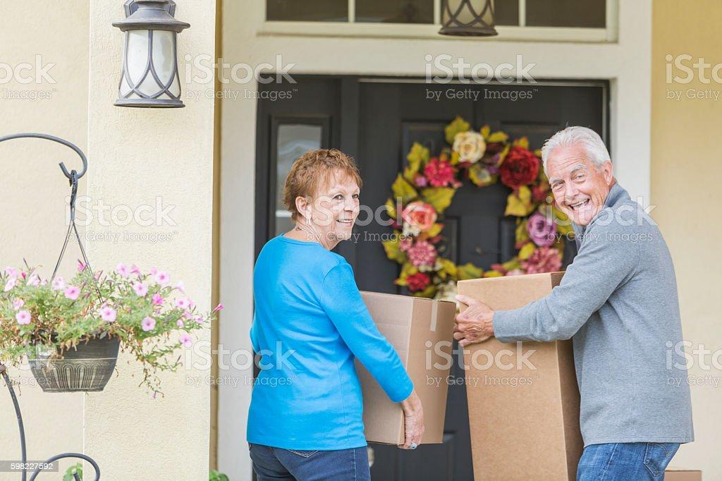 Sênior casal Carregando caixas a porta da frente de casa foto royalty-free