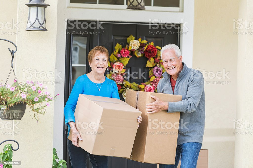 couple de personnes âgées porter les boîtes à la porte d'entrée de l'hôtel photo libre de droits
