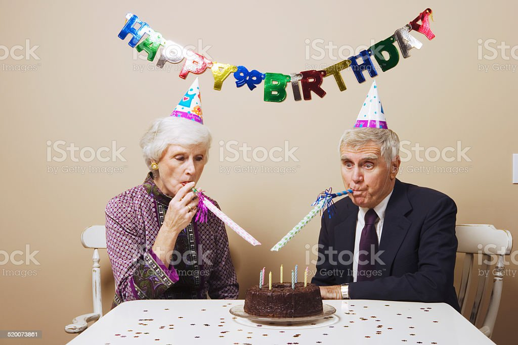 Senior couple celebrating birthday at dining room table stock photo