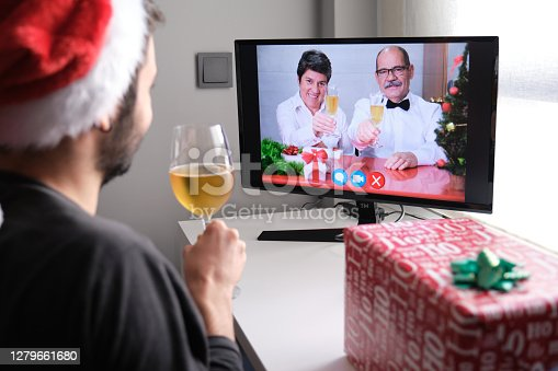 Senior couple celebrating christmas toasting with champagne on a video call with their son. Christmas celebration concept.