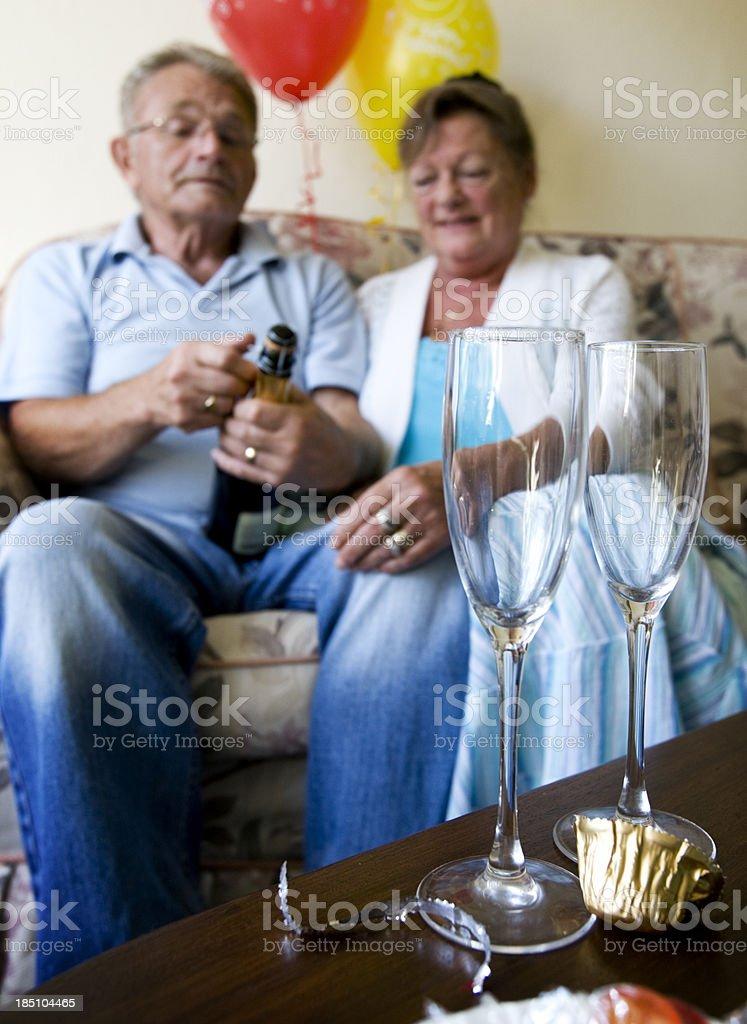 Senior couple celebrating something against a balloons stock photo