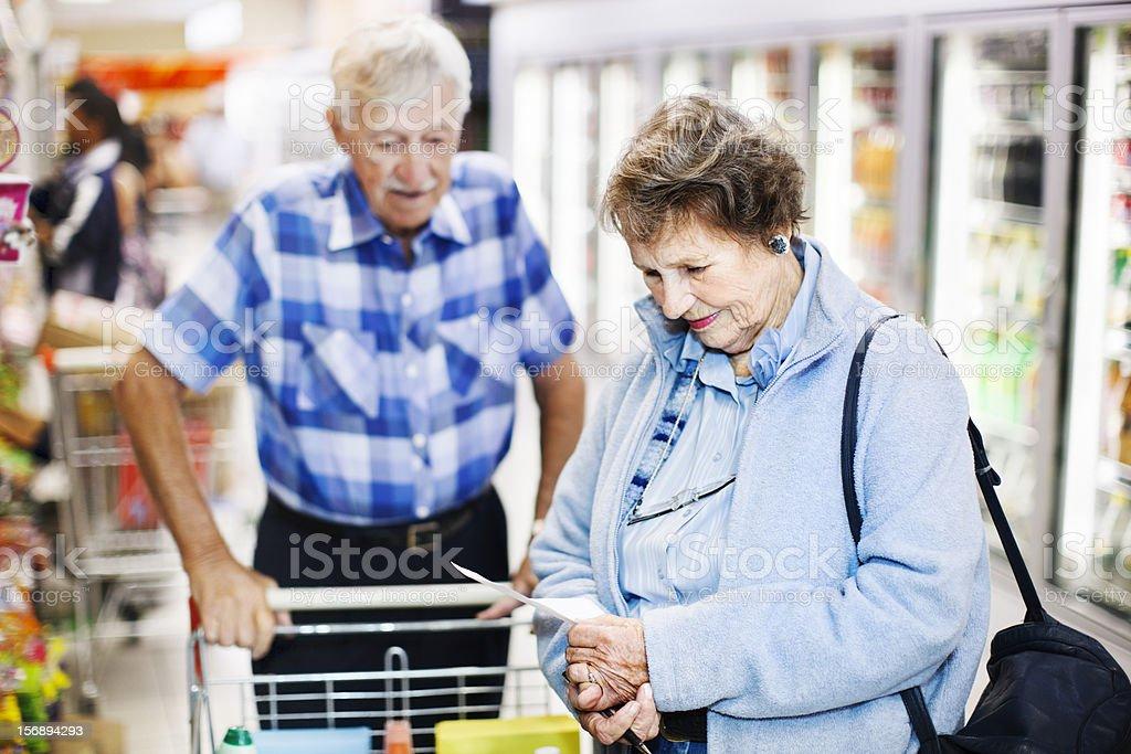 Senior couple check shopping list in supermarket aisle stock photo