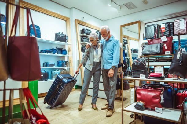 älteres paar wahl einen fahrbaren trolley koffer taschen und accessoires vorrätig - trolley kaufen stock-fotos und bilder