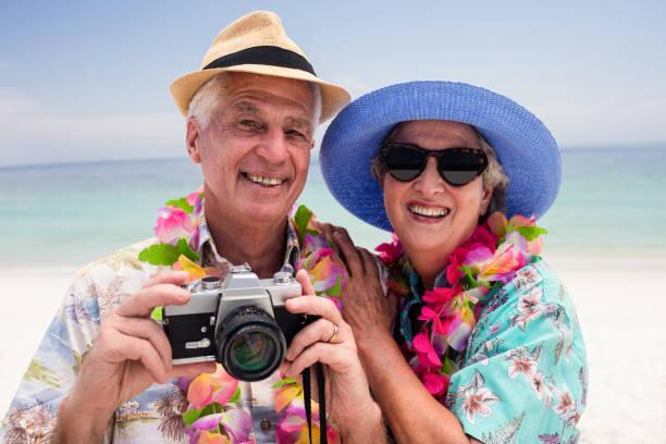 älteres paar klicken ein foto mit der kamera - senior bilder wasser stock-fotos und bilder