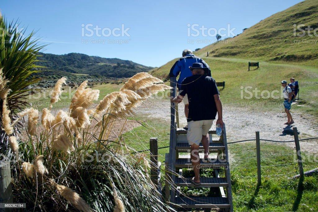 Senior Couple climbing Stile in Rural Scene stock photo