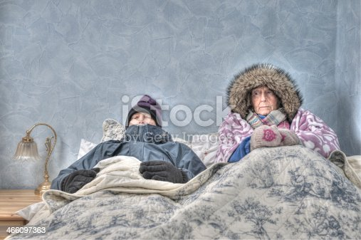 Senior couple, too cold to get out of bed, miserable, in inadequate housing, unable to afford heating. They are wrapped in blankets, wearing hats, scarves, gloves and winter coats.