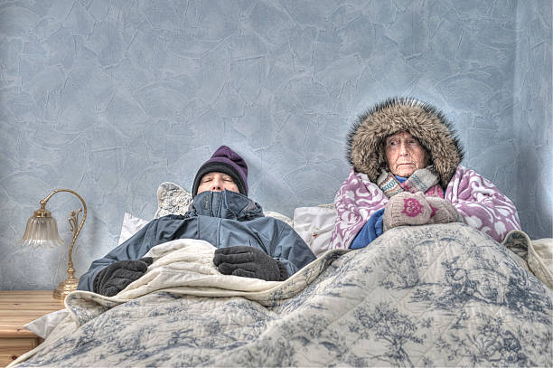 senior couple, cold and miserable in bed - warm clothing stock photos and pictures