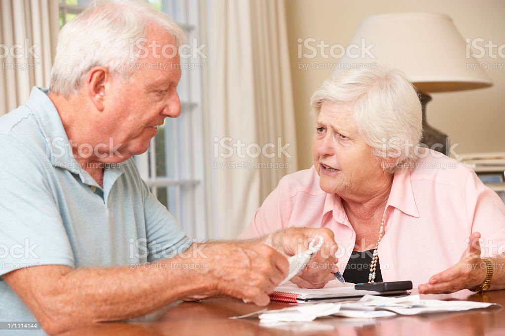 Senior Couple Concerned About Debt Going Through Bills Together royalty-free stock photo