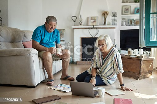 Wife and husband in 50s and 60s sitting in family living room with color swatches and tile samples enjoying coffee and imagining home improvements.