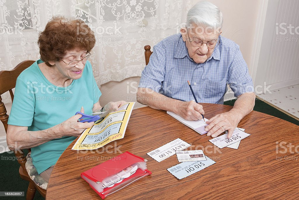 Senior Couple Cutting Coupons stock photo