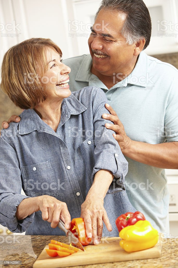 Senior couple cutting peppers together stock photo
