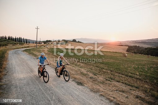 Senior couple are cycling along a dirt road in Tuscany at sunset.