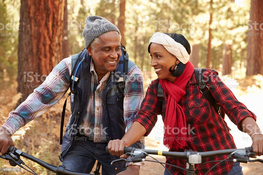 Senior Couple Cycling Through Fall Woodland stock photo