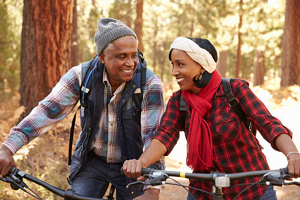 Senior Couple Cycling Through Fall Woodland stock photo